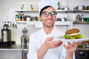 Happy chef serving hamburger on plate