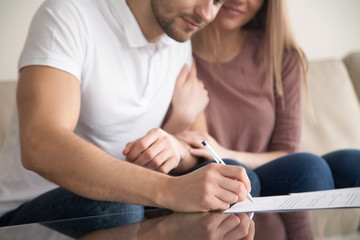 Close up of couple signing documents, young man putting signature on document, his wife sitting next to husband holding his arm, real estate purchase, first time home buyers, prenuptial agreement