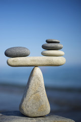 Balancing of black and white pebbles on the top of stone. Symbol of scales is made of stones.