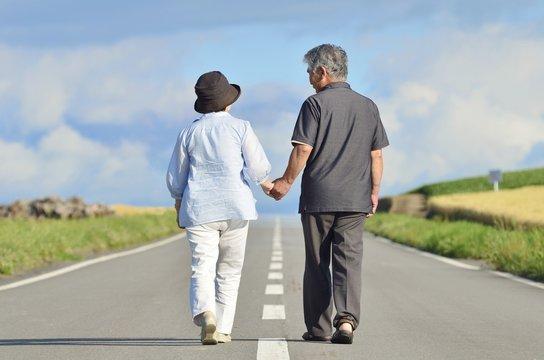 一本道を歩くシニアの夫婦