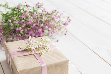 White wooden table with pink flowers and a present, mother's day concept