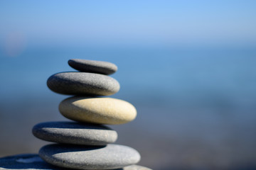 Zen spa stones with blue water and sky. Balanced stones background with copy space. Spa symbol. Beautiful picture. Symbol of stability. Stones pile background.