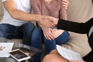 Female realtor meeting with couple, close up view of handshake after making successful real estate deal, renting or buying flat, young family investing in property, man shaking hands with broker