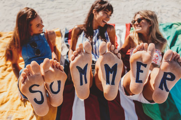 Bare feet of female friends with word summer