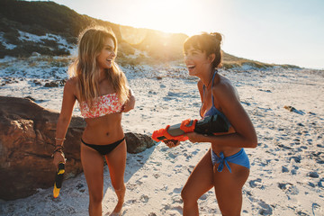 Happy friends playing with water guns on the beach