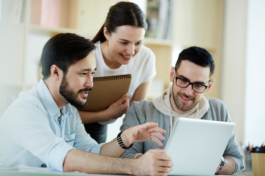 Group of people working with laptop together and smiling