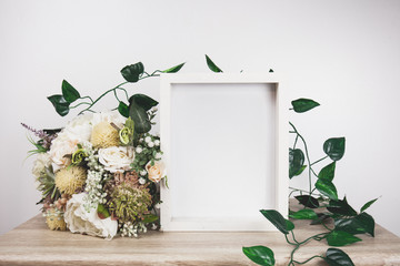 White frame mockup with flower and vine.