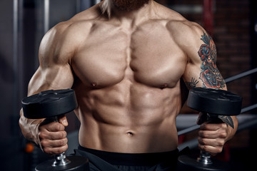 Athlete muscular bodybuilder  with dumbbells.
