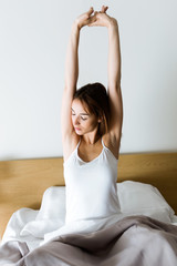 Beautiful young woman stretching in bed after wake up.