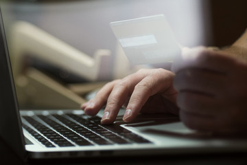 Hands with credit card and using laptop