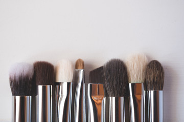 Makeup brushes on wooden background.