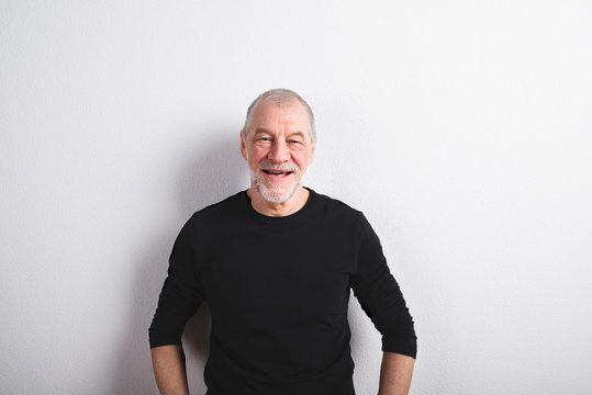 Senior man in black woolen sweater, studio shot.