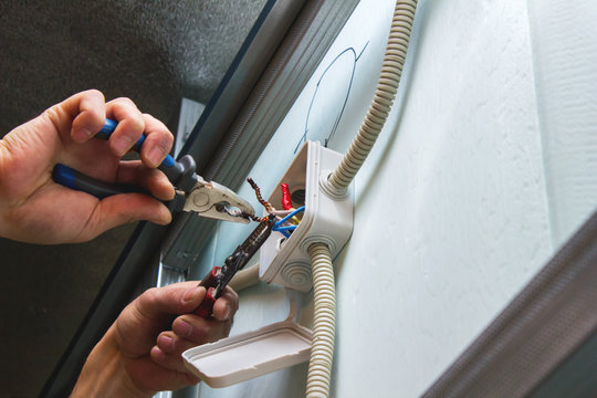 Installation of electrical boxes, the electrician mounts the electrical wiring inside the building