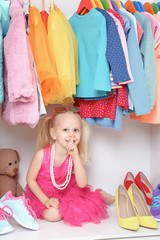 Cute small girl in wardrobe with clothes