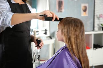 Cute little girl in hairdressing salon