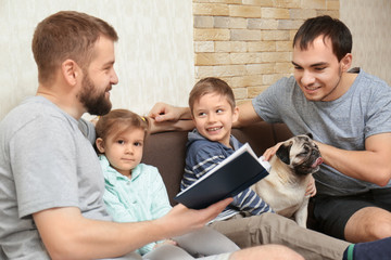 Male gay couple with children sitting on sofa at home