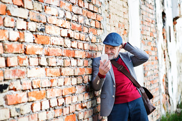 Senior man with smartphone against brick wall taking selfie.