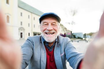 Handsome senior man in town taking selfie.