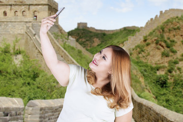 Happy woman taking selfie at great wall