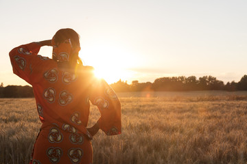 African woman in traditional clothes in a field of crops at sunset or sunrise