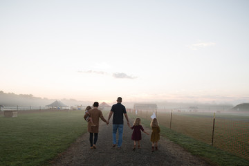 Family with three children walking on rural road