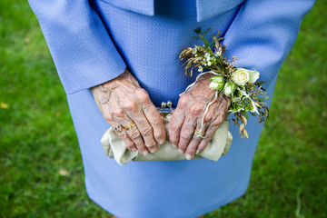 Elderly woman holding purse with flowers on wrist, high angle