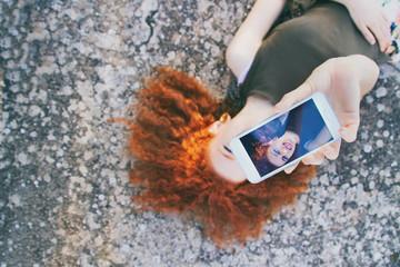 Adolescente pelirroja sacándose un selfie con su teléfono móvil
