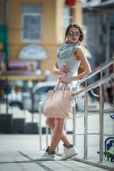 Beautiful brunette young woman wearing sunglasses, light jacket and handbag walking on the street