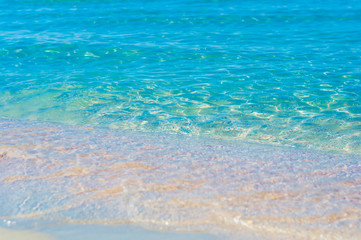 Soft sea waves wash over golden sand in a beach. Blured natural background