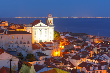 Scenic view of Alfama, the oldest district of the Old Town, with Church of Saint Stephen during evening blue hour, Lisbon, Portugal