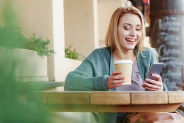 Young woman sitting outside the cafe with hot beverage