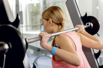 Careful athlete squatting with barbell in gym