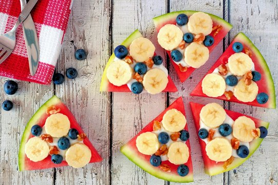 Sliced, juicy watermelon pizza with bananas, blueberries, nuts and yogurt, overhead view on rustic white wood