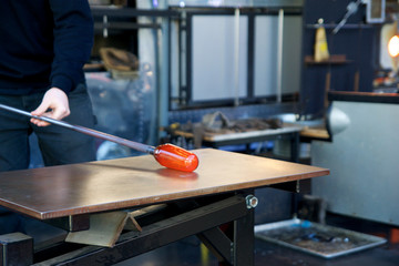 SEATTLE, WASHINGTON, USA - JAN 23rd, 2017: A man takes motlen glass and shapes it using some specialized tools for glassblowing art at an exhibit by American artist Dale Chihuly at Chihuly Garden and