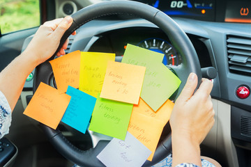To do list in a car on driving wheel - busy day concept