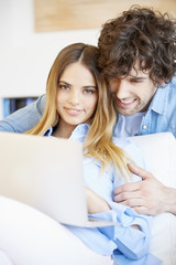 Spend time together. Shot of a smiling young woman and an affectionate handsome man relaxing at home and using laptop.