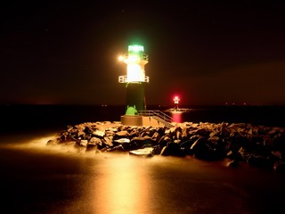 Green lighthouse shinning at the end of stony pier in dark night