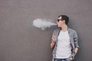 Young man smoking, vaping electronic cigarette or vape. Gray background