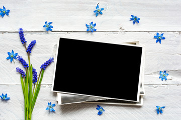 blank photo frame and spring blue flowers bouquet