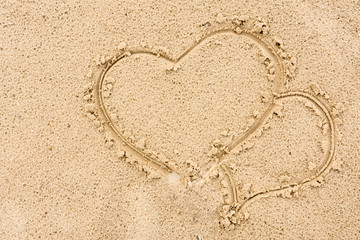 Two hearts painted enamored on the sand near the river background