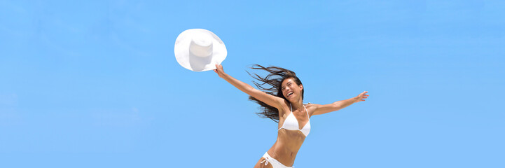 Wall Mural - Happy carefree vacation woman jumping of joy and freedom in the air with sun hat on summer beach. Blue sky banner background. Happiness travel holidays healthy lifestyle concept.