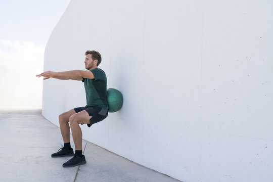 Strength training man doing squats using medicine ball rolling on wall squatting at fitness centre. Workout squat bodyweight exercises using medicine ball. Fitness athlete working out.