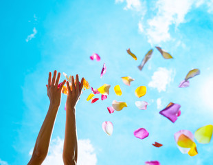 Wedding celebration and party concept. Hand throwing colorful rose pedals in the air.