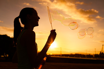 Silhouette of girl having fun blowing bubbles.