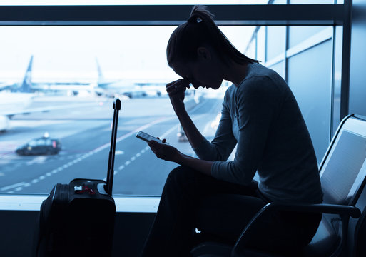 Stressed woman traveler waiting at the airport. Missing flight or getting bad news concept.