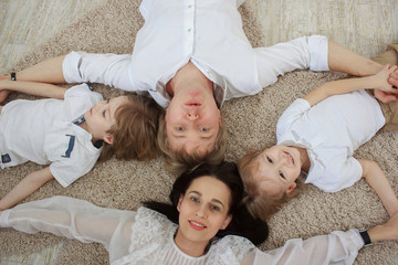 Top view of beautiful young parents, their cute little sons lying on floor