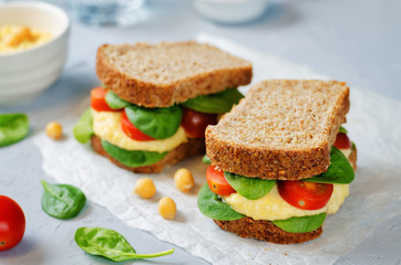 rye sandwiches with hummus, spinch and tomatoes