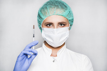 Doctor or scientist in blue gloves with syringe on white background