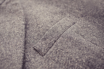 Closeup of light grey tweed woolen coat or jacket with a pocket fragment.