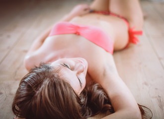 Young woman in swimsuit lying on the wooden floor
